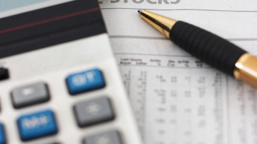 Stock market table analysis, calculator and pen indicates research and analysis, with cash, vertical orientation, shallow depth of field